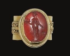 A ROMAN CARNELIAN RINGSTONE   CIRCA 1ST-2ND CENTURY A.D.   The convex oval stone engraved with Ceres, the goddess standing with her head in by chrystal