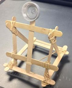 A photograph shows a small catapult structure made from Popsicle sticks, rubber bands and a plastic bottle cap.