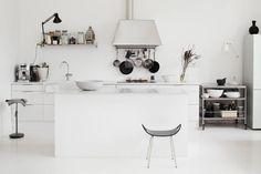 Valkoinen keittiö ja olohuone ovat yhtä avaraa tilaa. Keittiön uudistuksessa jätettiin yläkaapit pois. Saarekkeen tasoon käytettiin valkoisia 10 x 10 sentin laattoja. Sen alapuolella olevat laatikostot ovat Ikeasta. Isot valkoiset kulhot ovat syntyneet Pian ja Jenna Mayerin keramiikkapajassa.