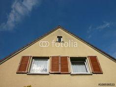 Zwillingsfenster mit Fensterläden aus Holz im Giebel der Fassade eines alten Wohnhauses in Großauheim am Main in Hessen