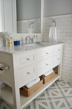 White and gray bathroom features top half of walls painted gray and bottom half…