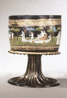 Late 15th century. Standing cup; blue glass; cylindrical bowl with notched applied ring at base; ribbed stem and spreading foot; bowl ornamented with enamels of various colours and gilding; two bands with procession scene between, including Venus, Hymen, centaur, cars, animals (goose), putti and draped figures; clipped trees in background.