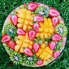 Fruit platter with strawberries, kiwis, green grapes, and mangos