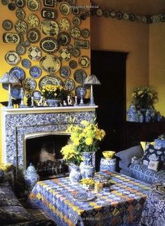 room decor ... Blue, white, and yellow ... porcelain collection hung on yellow wall .. luv the porcelain fireplace in white and blue ...