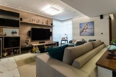 """Com 32 m², este home theater conta com um móvel de madeira que acomoda a TV de 50"""", além dos equipamentos, de um bar fechado, adega e cristaleira. As caixas de som foram distribuídas no móvel, mas também no forro e na parede. Para o conforto do espectador, um sofá, uma poltrona e a mesa de centro compõem a área de estar do projeto assinado pela arquiteta Margareth Zilo"""