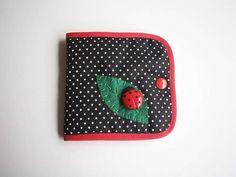 Fofinho porta absorvente com aplicação de joaninha e folha em feltro.  Acabamento em viés vermelho e botão de pressão.    Dimensão: 12 x 11 cm (fechado) R$ 15,00