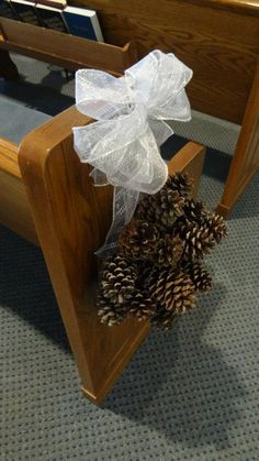 Possibility?!?! Pinecone - Winter Wedding Decor!!  I made these aisle runners myself.  We cut a styrofoam ball (5 in) in half and painted brown, then pinecones hot glued in the pattern of my choice.  Small ribbon (not seen in picture) pinned (using floral pins).  The entire thing is hung from a plastic pew clip.  The big silver bow covers the clip and adds a little pop of color and glitter :)