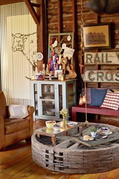 This living room makes use of decor that is both beautiful and functional. Cooper found an old factor gear at Brimfield, turned it on its side, and topped it with sheep fencing for a cool cocktail table. Corrugated metal gets an artistic upgrade with a giant hand-painted butcher chart. The wall retracts and provides access to the back patio.