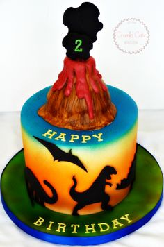 - Dinosaur themed birthday cake.  Fondant silhouettes, fondant volcano and airbrushed colors.  By Crumbs Cake Boutique.