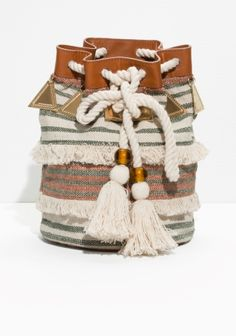 Heavily woven canvas lends a free-spirited air to this artisanal bucket bag. Ornamented with brass charms, pompom tassels, leather trims and chunky ropes, it makes for an inspiring festival companion.