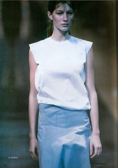 Young Giselle Bunchen wearing minimalist fashion by Jil Sander Spring Summer 1999. Plain white shirt and a blue skirt, probably looks boring for people loving the fashion of the previous decades