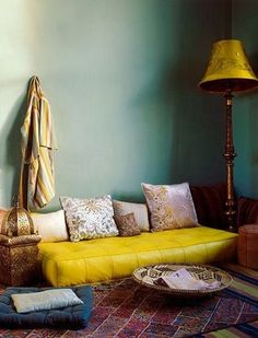 Yellow pouf couch cushion--turquoise wall--yellow lamp