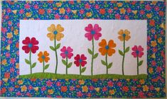 """Designed by: Michele Foster Finished size: 38"""" W x 22"""" H (adjustable) Skill Level: Beginner Techniques: Fused appliqué, pieced borders Price: $2.95 (USD) Format: PDF file (download and save instant..."""