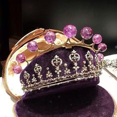 A delicate diamond tiara with seven larger foliate motifs and smaller spacers; with what looks like a nine amethyst cabochon tiara behind it, sharing the same case. (The amethyst tiara looks like so many lollipops, or maybe light bulbs.)