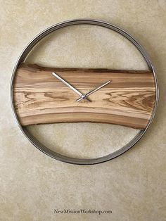 "This 20"" diameter wall clock features a steel outer rim with an Italian Olive wood live edge slab. The slab is finished in bee's wax. The contrast between the cold chrome steel and the warm beautiful Olive wood makes for a fantastic piece. The movement hands are a matching chrome.  THIS IS THE ACTUAL PRODUCT YOU WILL RECEIVE, NOT A SAMPLING OF A PIECE TO BE MADE FOR YOU.  Hanging hardware included; simple to mount.   Requires one ""AA"" battery."