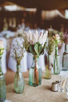 Wedding Flowers A simple idea for an eco wedding - recycled glass bottles as stem vases - Top tips and inspiration for beautiful and eco-friendly wedding decorations Protea Bouquet, Protea Wedding, Floral Wedding, Boho Wedding Flowers, Deco Champetre, Rustic Wedding Centerpieces, Simple Wedding Table Decorations, Wedding Vases, Rustic Wedding Decorations