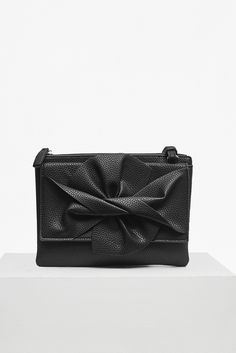 <ul> <li> Grainy faux-leather bag with three compartments</li> <li> Large twist bow front detail</li> <li> Magnetic-fastened flap compartments at either side of main zipped pouch</li> <li> Detachable and removable cross-body straps —  to convert into a clutch</li> <li> Lined interior</li> <li> <strong>W:</strong> 25cm  <strong>H: </strong>18.2cm  <strong>D:</strong>5cm</li> </ul>