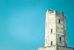 Old white tower with blue sky by Nuchylee Photo on Creative Market