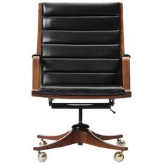 executive desk chair by Edward Wormley  USA  1950's  A bent laminate walnut armchair with channeled black leather on casters.