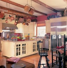 Huge island with tons of storage and rustic wood beams are great too! Garrison Colonial Home Kitchen Photo from houseplansandmore.com