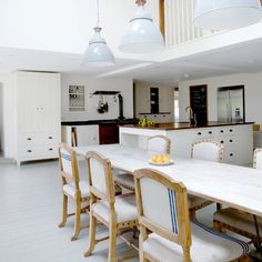 Kitchen-diner with white cabinetry, island unit with wood worktop, red range cooker and white dining table
