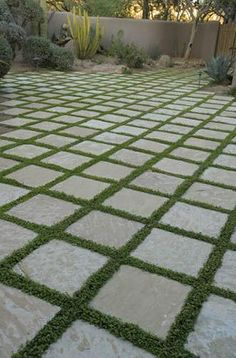"""We like the way A Tile Guide describes the paving in this photo as having """"grass for grout"""". Twelve-by-twelve stone tiles are laid out in a grid, with grass in the joints instead of grout..."""