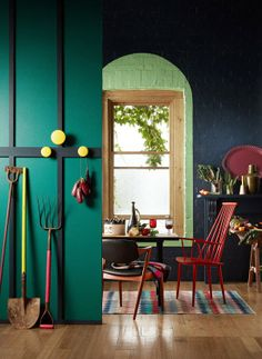 Emeral green walls combined with black and green. Bright furniture incl. red chairs