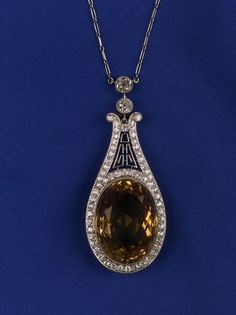 Art Deco Platinum, Diamond and Citrine Pendant, the teardrop form centered by a large, oval faceted citrine, further set with approx. fifty-nine old European-cut diamonds, honeycomb pattern gallery, millegrain accents, completed by a paperclip link chain with two diamond drops, signed M. & Co. for Marcus & Co. , lg. 17 1/2 in.