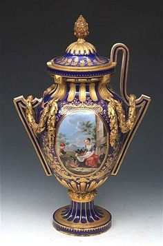 "A SEVRES COBALT BLUE GROUND VASE and cover (vase Grec or Greque rectifier), having a reserve painted panel with 2 young children outside a stable, the reverse with trophy designs, having gilt swags to the handles, acanthus leaf finial and with fluted decoration, old repairs, (cracks and 1 part handle missing), 18 1/4"" high"