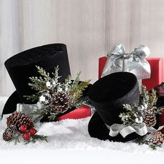 Jaunty and unexpected, our Charming Top Hats offer a refreshing new element to your holiday displays. These black felt hats are decorated with a festive ribbon, silver ornaments, and flocked pine branches that suit the season. The small one is sized to be nestled among the branches of a Christmas tree. The larger one integrates nicely into tabletop displays. Neither is an actual hat  there is no opening at the bottom, so it will retain its shape better over time.                    Top ...