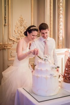 Lovely couple slices their triple layer wedding cake