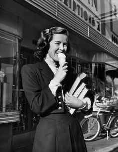 A young woman enjoys an ice cream cone outside of a local drugstore; 1945