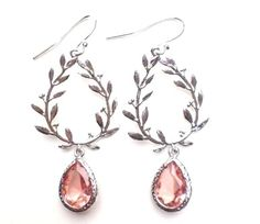 These earring are simply gorgeous with there beautiful Silver design and stunning crystal charm in the Padparadscha inspired hue. These romantic stunners are surely to become your favorite go-to earrings. Handmade with love Sterling Silver Plate Tarnish Resistant Hypo Allergenic Length about 2 inches Length 2 Inches