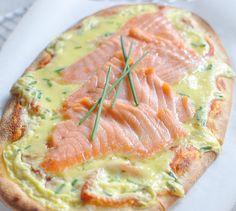 Fouetter la ricotta avec les œufs, la ciboulette hachée. Saler et poivrer.   Étaler votre pâte à pizza et verser dessus la moitié du mélange.   Déposer le saumon fumé et verser le reste du mélange.   Badigeonner avec le jaune d'œuf.   Cuire au four à 180°C environ 30 mn.