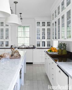 """Island houses need clean white kitchens,"" says Lindroth. She painted walls and cabinets White Dove in Aura and the ceiling Decorators White in Waterborne Ceiling, both by Benjamin Moore. Pendant fixtures, Visual Comfort."