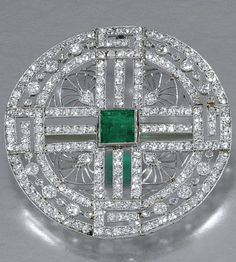 EMERALD AND DIAMOND BROOCH/PENDANT, CIRCA 1910 Centring on a square-cut emerald, inset to a circular plaque of open work design, millegrain-set with single- and circular-cut diamonds, brooch pin detachable, pendant fitting deficient.
