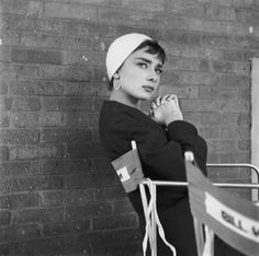 Hepburn takes a minute to herself on the set of Sabrina, the film that eventually made her a massive star. She's wearing a hat by Hubert de Givenchy, whose designs she would become famous for wearing.