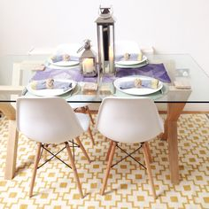 Scandinavian style dining area - John Lewis oak and glass dining table. White Eames chairs. The John Lewis accessories and IKEA rug add a splash of colour.