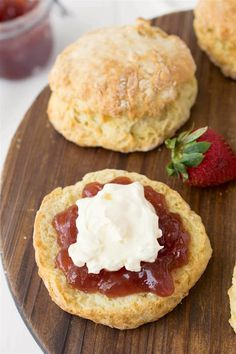 A closeup image of an English scone topped with clotted cream and strawberry jam