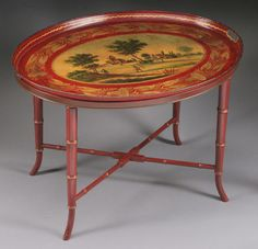 AN ENGLISH PAINTED TOLE TRAY 19th Century. Oval in form, painted with a figural landscape within a wreathed border, on a later faux bamboo stand.