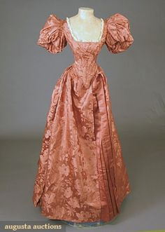 """PERSIMMON SILK BALL GOWN, c. 1895 2-piece, large scale floral brocade w/ pleated plain satin center skirt panel, boned bodice w/ puff sleeve, back laces, points front & back, neckline w/ lace trim, label """"Joseph Johnson Leicester"""", B 33"""", W 20"""", Skirt L 44""""-61"""""""