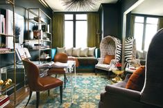 """huge mirror """"doubles"""" space; lucite desk """"disappears""""; open-sided shelves permit """"visual breezes""""; dark walls """"recede""""; lovely patterned rug draws attention down which gives illusion of higher ceiling."""