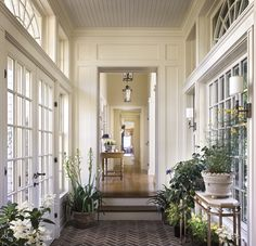 Herringbone brick floored garden room/entry with french doors, and symmetrical windows opposite, sconces, lovely millwork, beadboard ceiling, and beautiful semi-circular transom windows leads into the main hallway of the house
