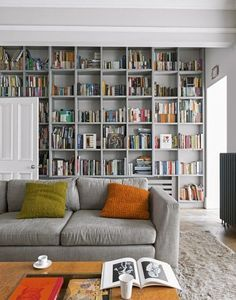 This grey living room with floor to ceiling bookcases uses a very uniform shelf structure but displays the books themselves in a random, jumbled way, creating a unque and interesting feature wall