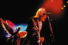 Kurt Cobain performing with the 'In Utero' angel behind him.