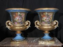 - Available to view in the Canonbury Antiques Hertfordshire showroom, just 25 minutes north of London<BR>  - Absolutely gorgeous pair of large Sevres style campana urns <BR> - Intricate and very bright floral displays really make these stand out <BR> - Large pair just waiting for some complementary flowers to flow out of the top <BR> - Nice tone of navy blue offest by the gold leaf painted designs <BR> - Please see close up of Sevres factory stamp on the underside <BR> - Purchased from a…