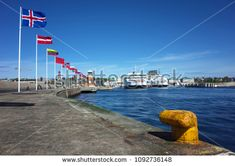 Helsingborg, Sweden - 04 May, 2018: Europe country flags swinging at harbour and Scandlines ferry boat cruising from Helsingborg Sweden to Helsingor Denmark