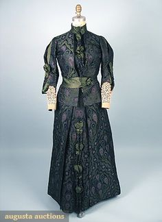 1890s silk afternoon dress by Worth.  Black satin w/brocade in bottle green, blue and mauve peacock feather pattern w/green satin ribbon, lace cuffs, and beaded bauble trim.