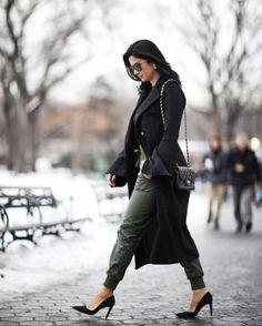 Look de inverno Constanza Fernandez: na tendência do verde militar numa track pants (calça estilo jogging) de couro, body preto, estilo camisa com manga fluída, colete longo e scarpin preto.
