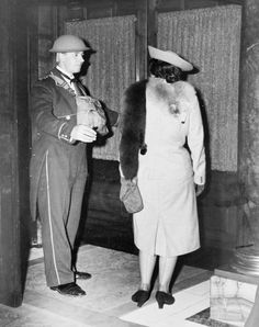 Westminster, London, October 1940: Doorman at the Trocadero wearing a tin hat. The Trocadero was an elegant restaurant near Piccadilly Circus. Here the doorman, wearing a protective tin hat, greets a customer. The bag round his neck possibly contains a gas mask. (Photo by Museum of London/Heritage Images/Getty Images)